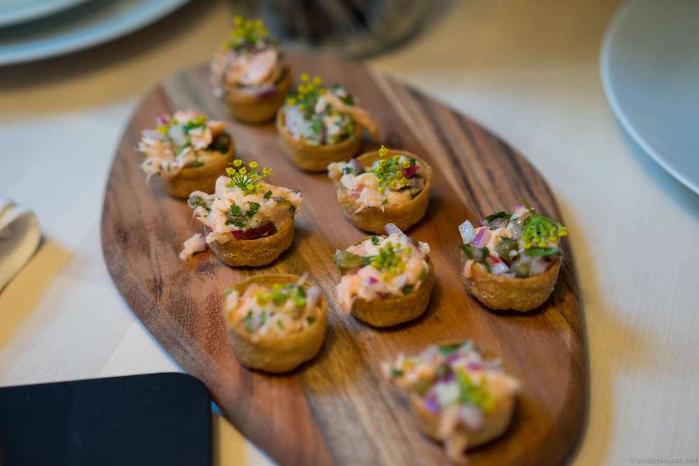 "An amuse bouche of pickled salmon, capers, red onion, lemon, olive oil and ""krondill"" awaited us at the tables"
