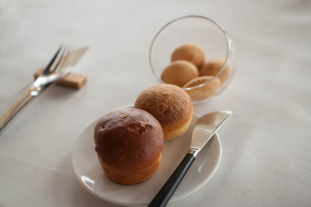 Brioche bread, soft roll and some crispy crackers.