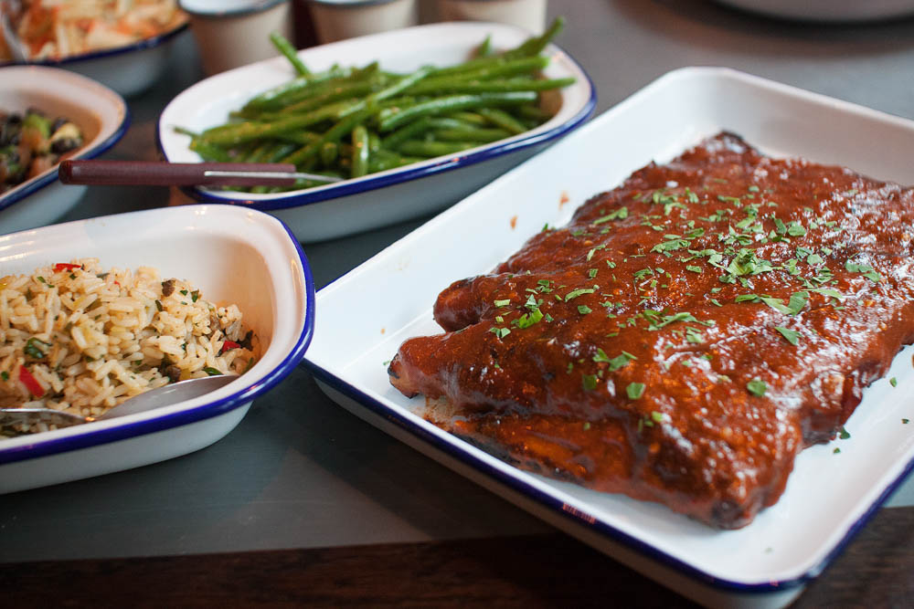 "St. Louis spareribs on the right. Green beans in the back and ""dirty rice"" with chicken liver on the left."