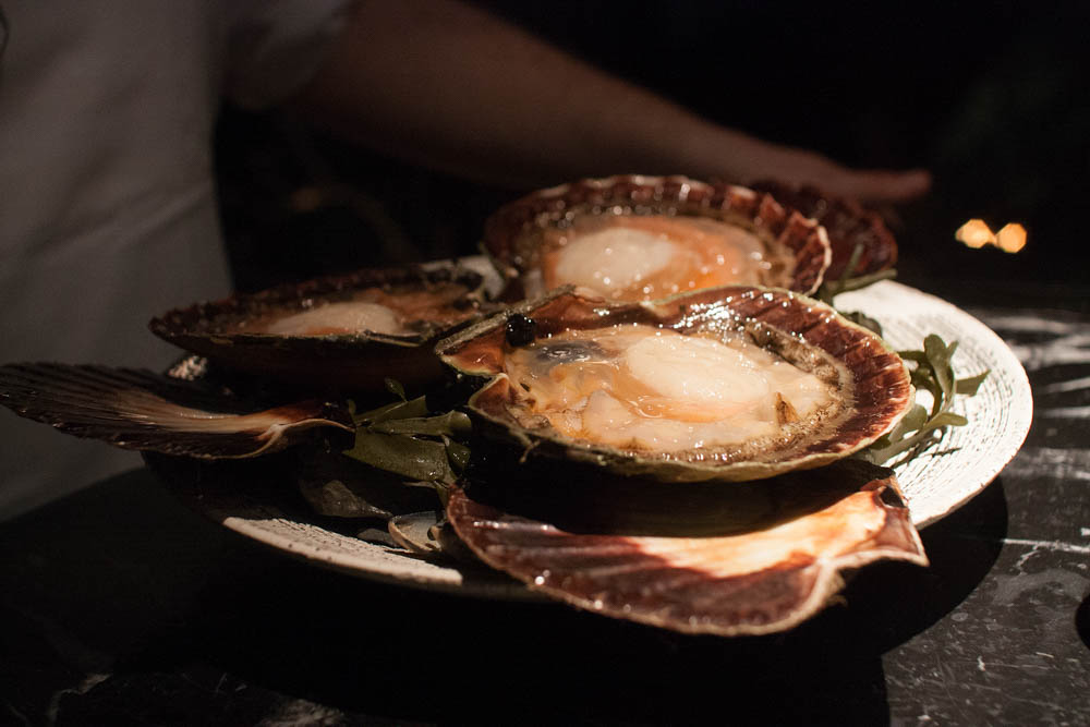 The scallops were presented at the table in their raw form, and the chef explained what they were about to do with them.