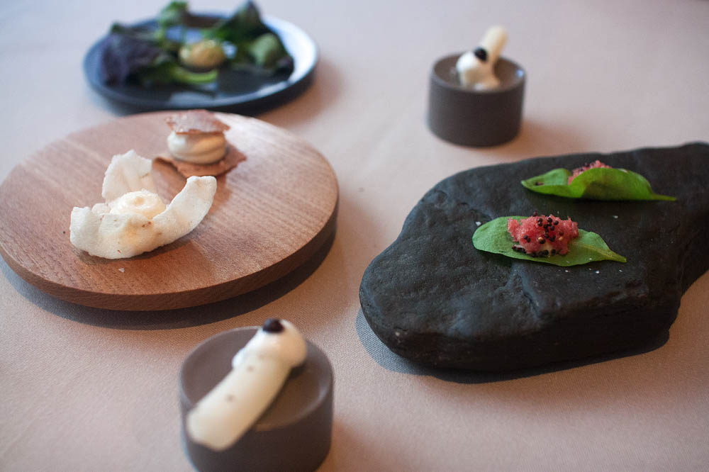 A variety of snacks before the actual menu. Last year's salsify with a juniper berry in the front. Lamb tartar on a sorrel with mustard seeds on the right. Flat breads with goat milk cheese on the left. Pak choi with marigold mayo in the back