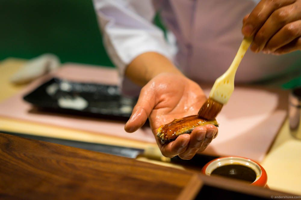 The eel is brushed with an unagi sauce by Roger