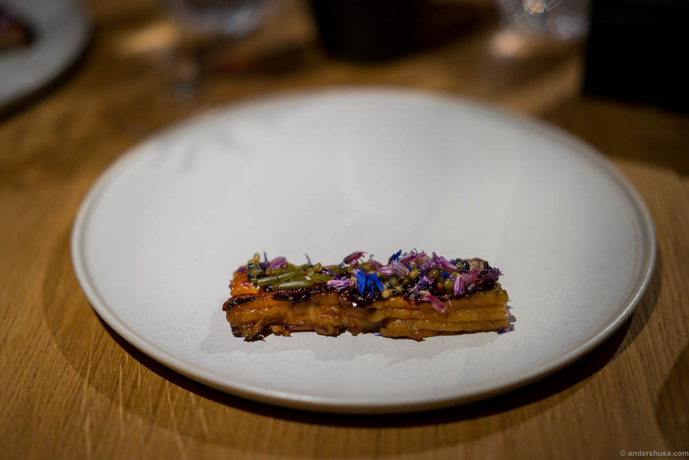 Fire roasted pork belly, black garlic, blackcurrant and salted flower buds at restaurant Kadeau in Copenhagen, Denmark