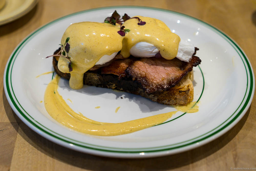 Sourdough bread, smoked bacon, poached eggs and browned butter hollandaise at restaurant Milk in London, UK.