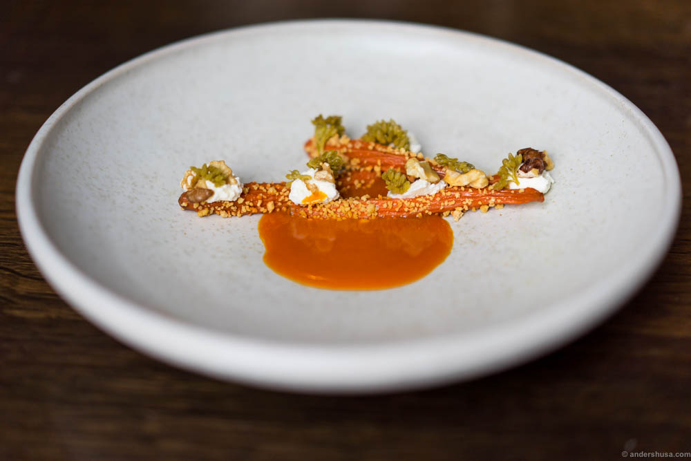 Dehydrated carrots rehydrated in their own juice, pickled orpin flowers, sour curd & concentrated carrot juice with browned butter at restaurant Amass in Copenhagen, Denmark