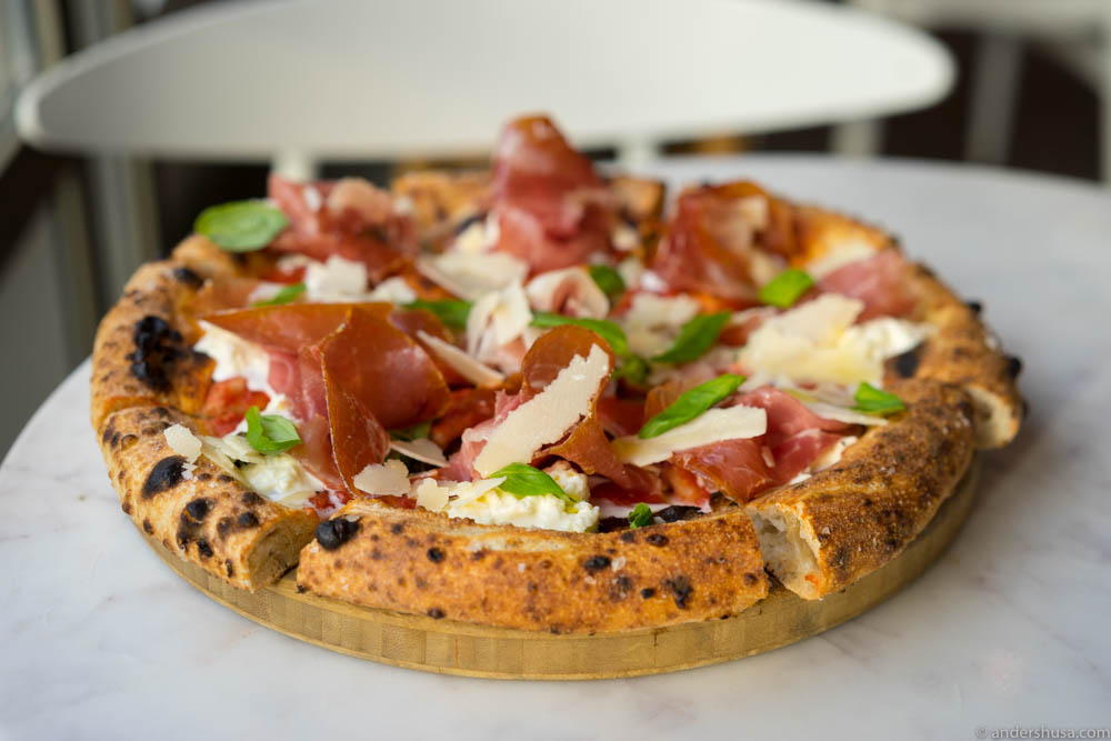 Sourdough pizza with cured ham, basil & parmesan on red tomato sauce