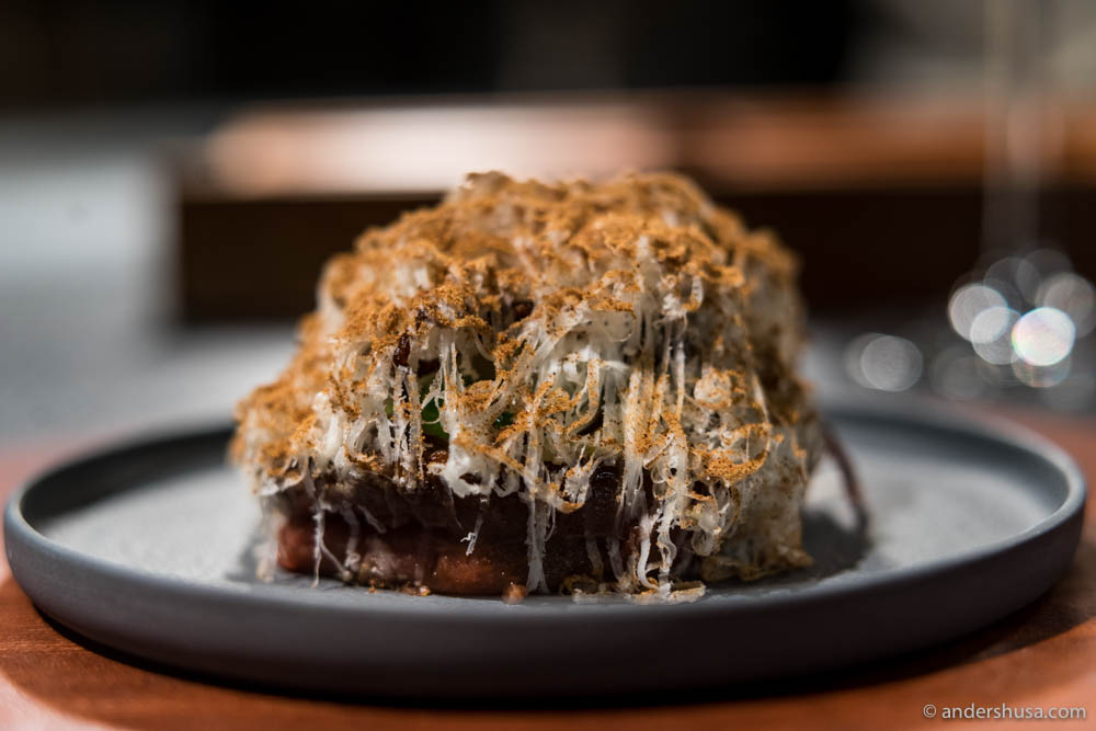 "Black Angus tartar cooked with ""fire oil,"" and served with black bread, pepper glaze, arugula mayonnaise & pickled fennel"