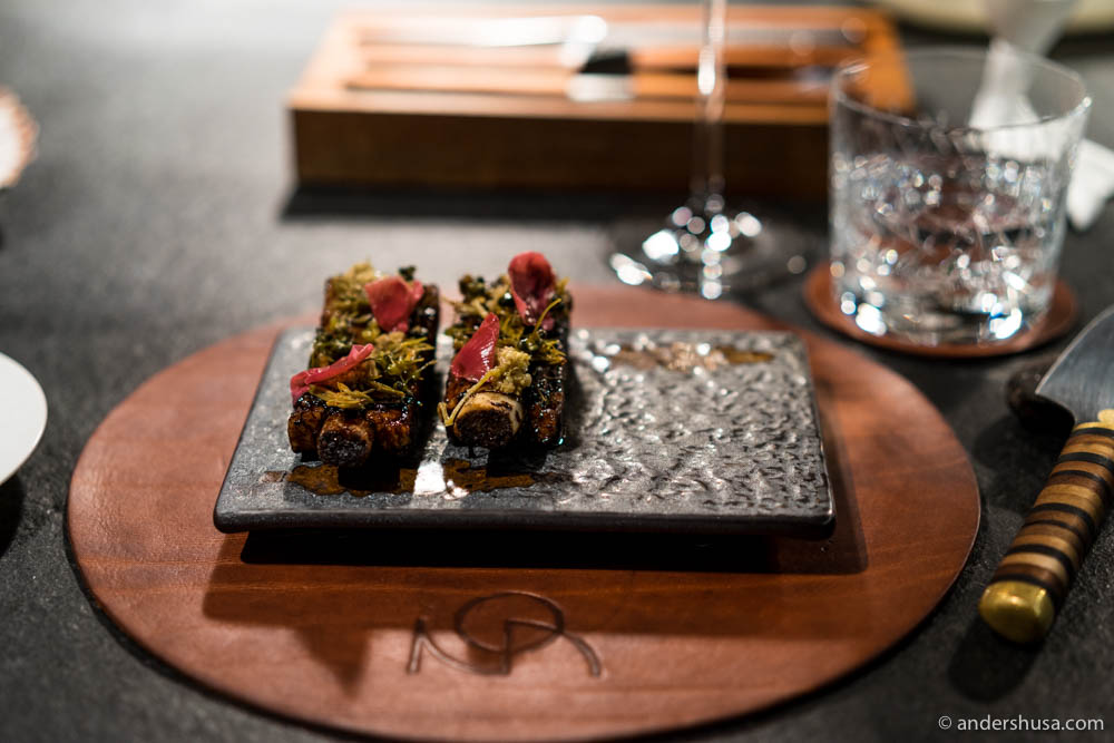 BBQ pork ribs glazed with elderflower syrup, served with pickled rose petals, pickled ramson capers, fermented spruce & elderflower blossoms at No. 21 – NOA Chef's Hall in Tallinn, Estonia