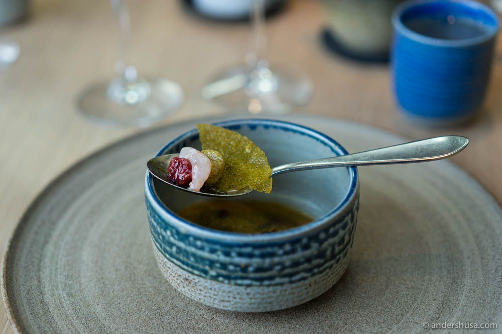 Raw Norwegian shrimps with green strawberries, dried tomatoes, and red gooseberries in an acidic broth with a crispy lid made of shrimp broth.