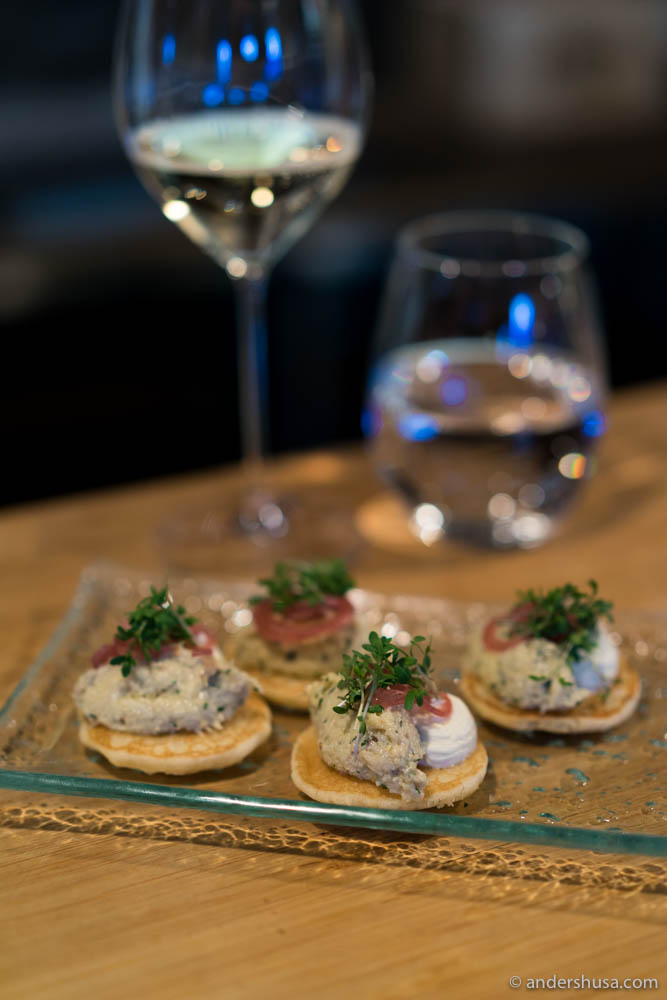 Small amuse bouche of blinis with brown crab, smoked sour cream, pickled onions & cress