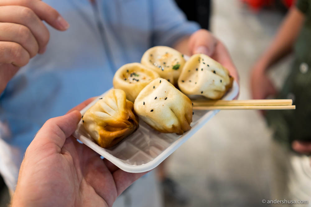 A Shanghai style pan-fried soup bao (Sheng Jian Bao) at no.25 – Dong Men Ding Food Street in Shenzhen in China.
