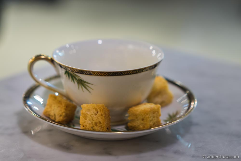 Melted cheese in a cup with a side of croutons.