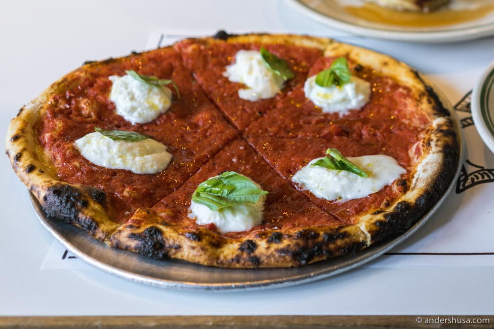 """The """"L.A. Woman"""" pizza is topped with tomato, burrata, olive oil, and basil."""