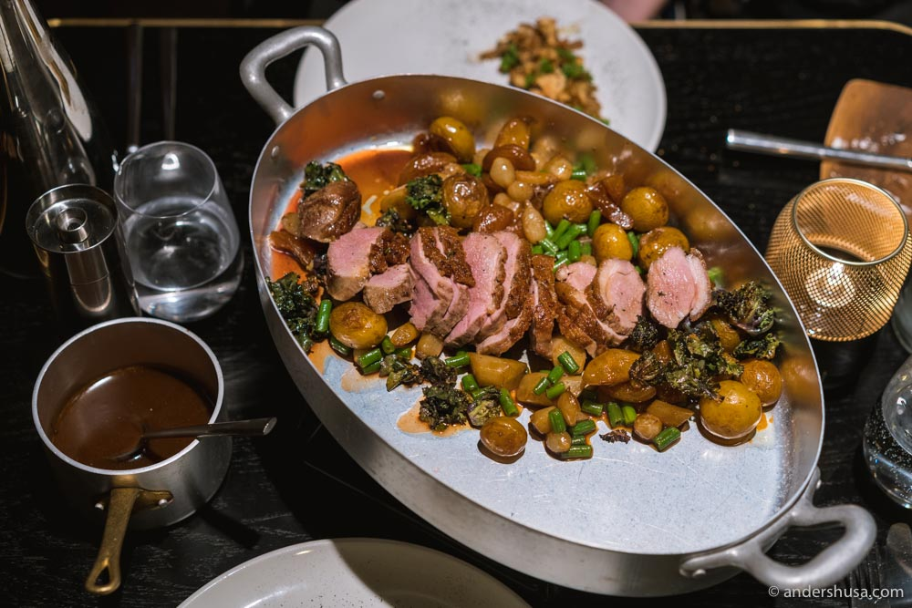 Duck with kale, potatoes, green beans, white asparagus, and a port wine sauce.