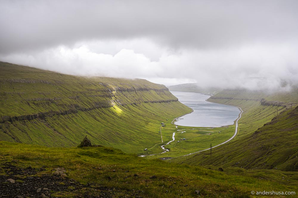 The fog rolling in over a Faroese fjord.